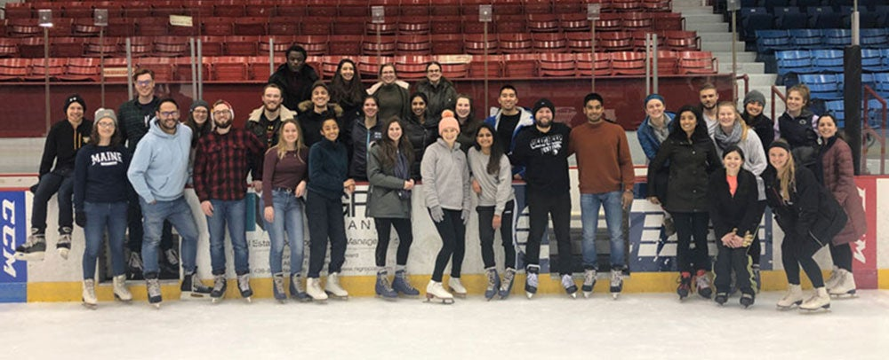 Group of grad students pose for a picture while ice skating