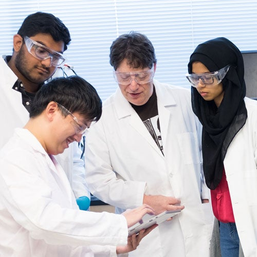 Professor and three students review lab data on a ipad